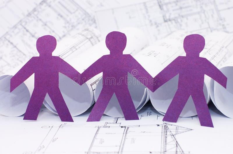 Homens pequenos de papel no projeto da casa imagem de stock