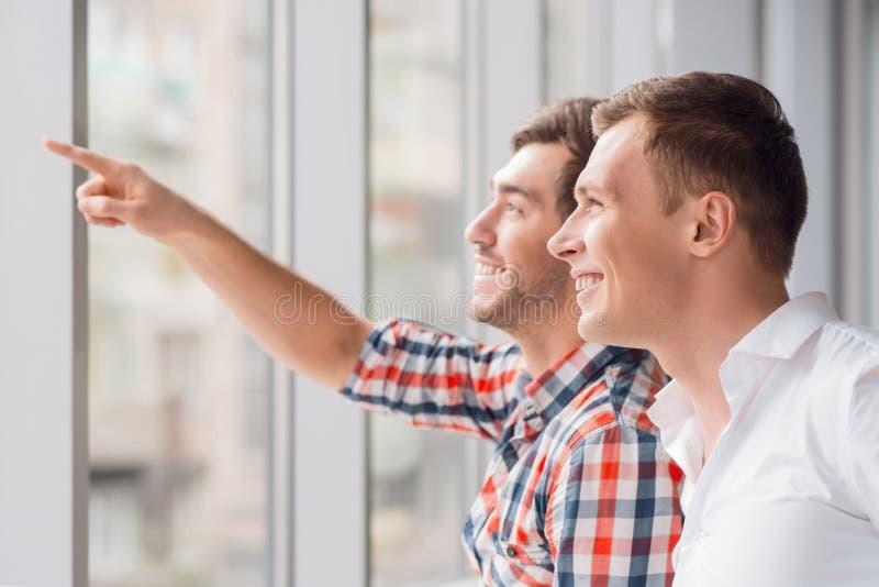 Homens positivos que estão a janela próxima fotos de stock