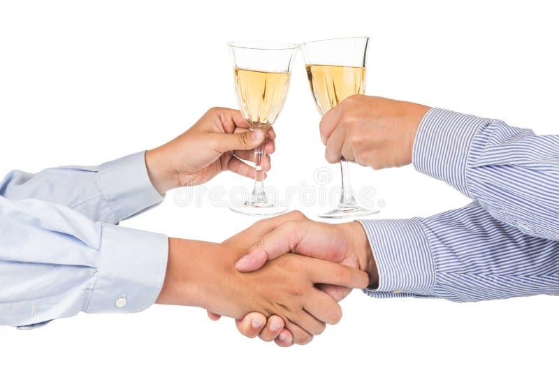 Homens que agitam as mãos e que brindam o vinho branco no cristal imagens de stock