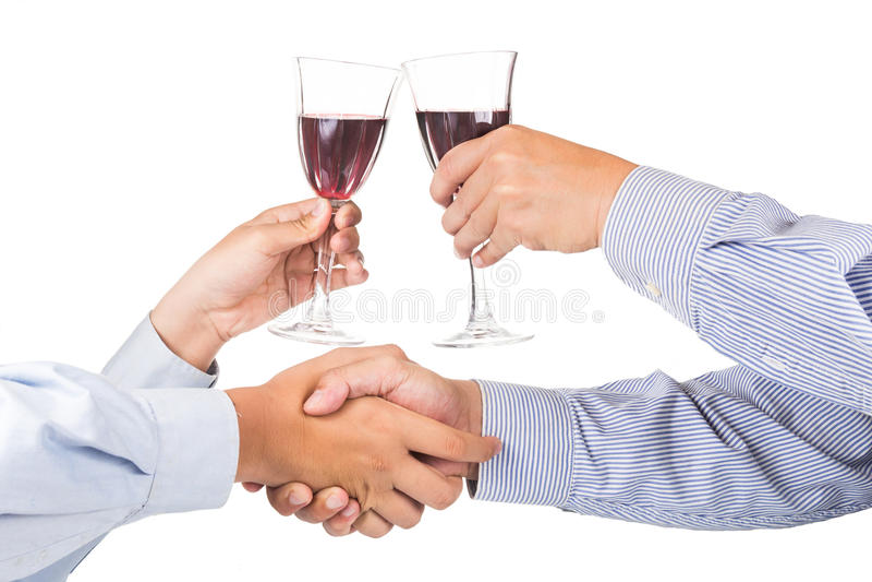 Homens que agitam as mãos e que brindam o vinho tinto no cristal fotografia de stock