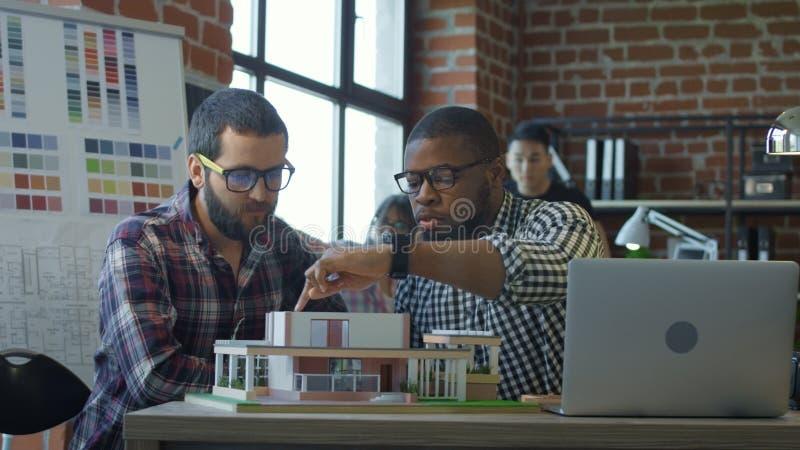 Homens que colaboram no projeto da casa nova fotos de stock