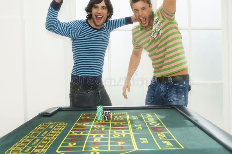 Homens que comemoram na tabela da roleta foto de stock royalty free