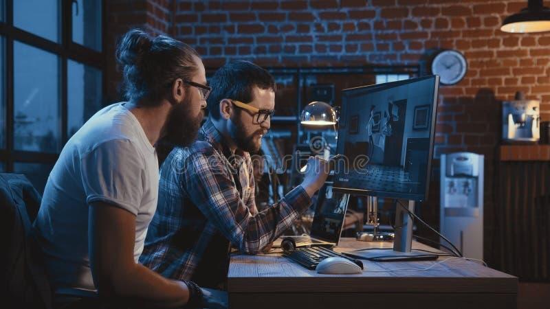 Homens que criam desenhos animados no computador imagens de stock
