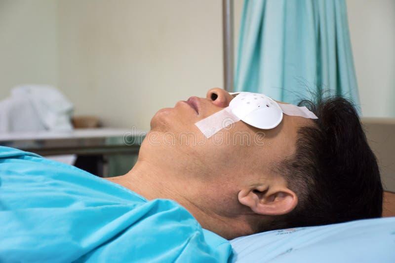 Homens que dormem e para usar a proteção do protetor do olho após a cirurgia do olho na sala de hospital imagens de stock