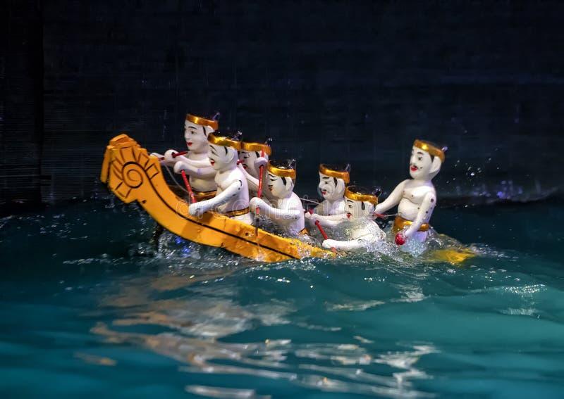 Homens que enfileiram fantoches de uma água do barco no teatro longo do fantoche da água de Thang, Hanoi, Vietname imagens de stock royalty free