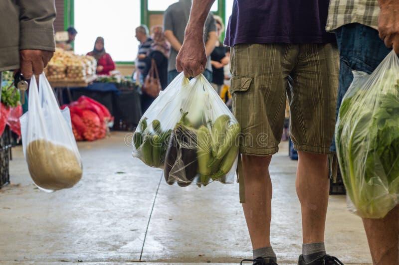 Homens que guardam o saco de compras plástico com vegetais em um bazar turco típico do greengrocery foto de stock royalty free