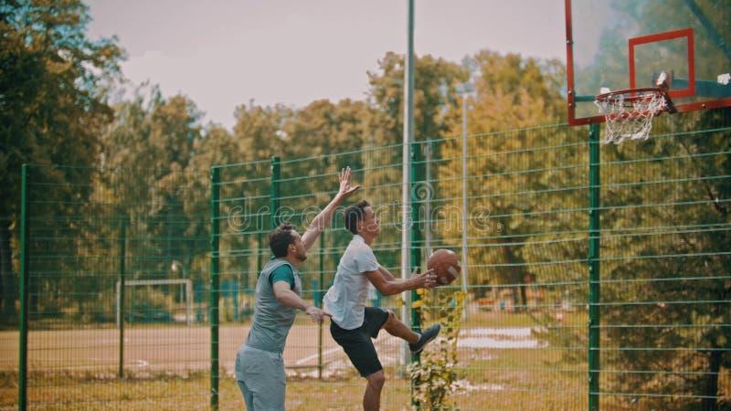 Homens que jogam o basquetebol no ar livre da terra de esportes fotos de stock royalty free
