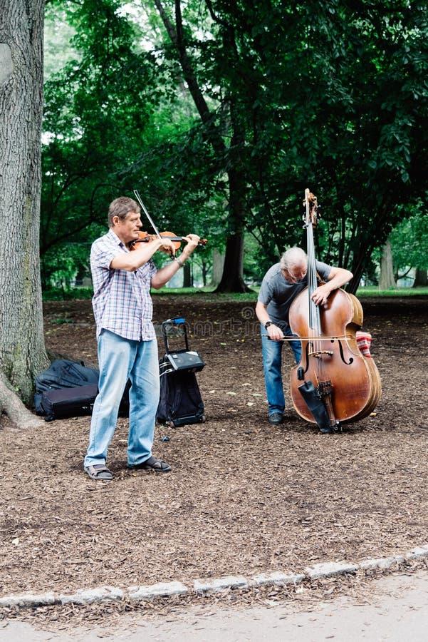 Homens que jogam o violoncelo e o violino no Central Park em New York fotos de stock