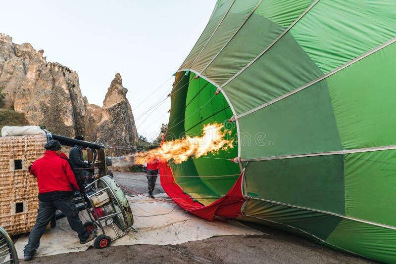 homens que lançam o balão de ar quente no parque nacional do goreme, cappadocia, peru imagens de stock royalty free