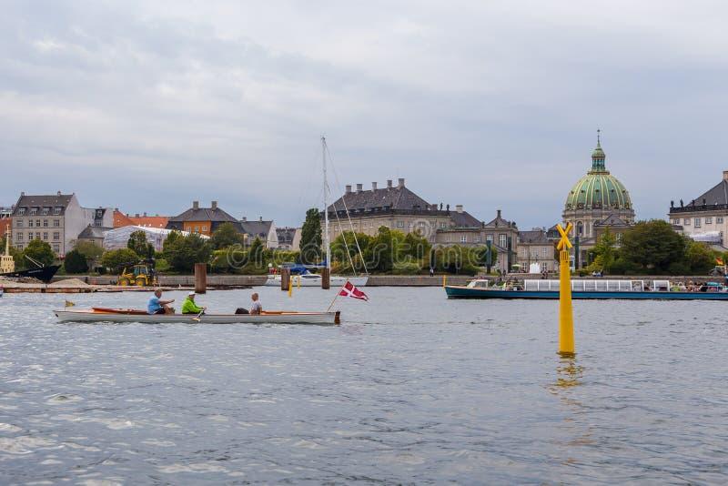 Homens que navegam no canal de Oresund no centro de Copenhaga, Dinamarca imagem de stock