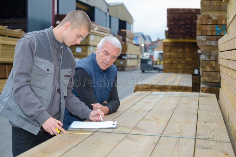 Homens que olham a prancheta e que medem a madeira fotografia de stock royalty free