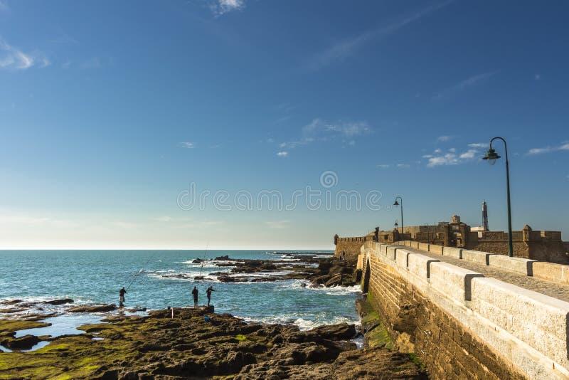 Homens que pescam fora das rochas de Paseo Fernando Quinones em Cadiz imagens de stock