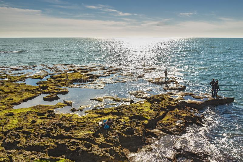 Homens que pescam fora das rochas de Paseo Fernando Quinones em Cadiz fotos de stock royalty free