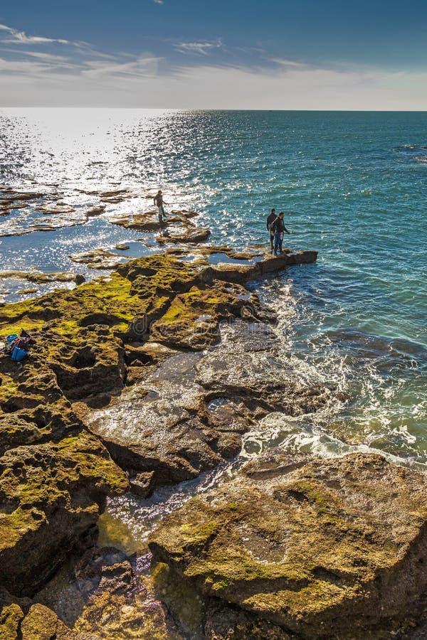 Homens que pescam fora das rochas de Paseo Fernando Quinones em Cadiz foto de stock royalty free