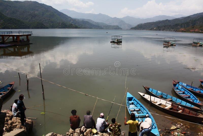 Homens que pescam no lago Pokhara Nepal foto de stock