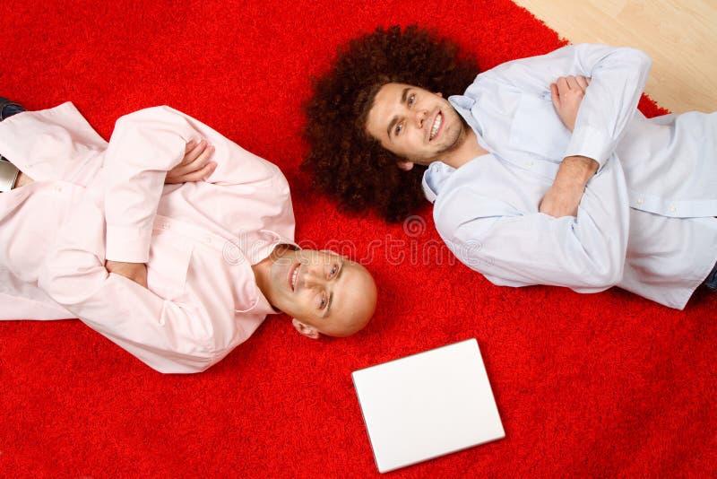 Homens que relaxam no tapete fotografia de stock royalty free