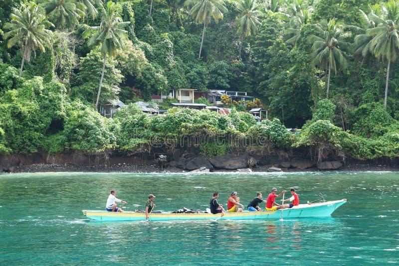 Homens que remam pelo cemitério na ilha tropical Lembeh imagem de stock