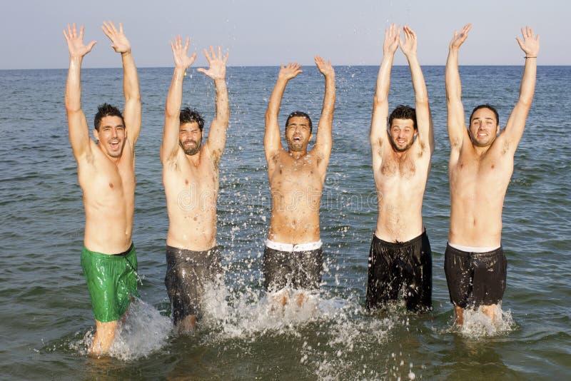 Homens que têm o divertimento na praia foto de stock