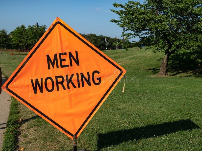 Homens que trabalham o sinal do constrction afixado acima em uma área do parque fotografia de stock royalty free