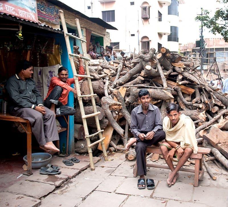 Homens que vendem a lenha para piras funerárias fúnebres hindu no banco do rio Ganges foto de stock royalty free
