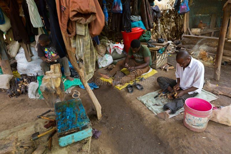 Homens tanzanianos locais que cinzelam a madeira na terra na vila de Mbu do wa de Mto, região de Arusha, Tanzânia foto de stock