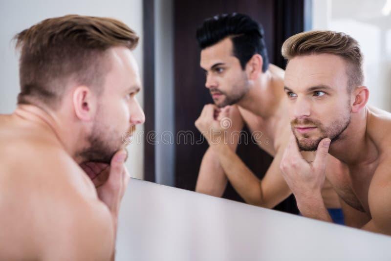 Homens Unsmiling na frente do espelho fotos de stock
