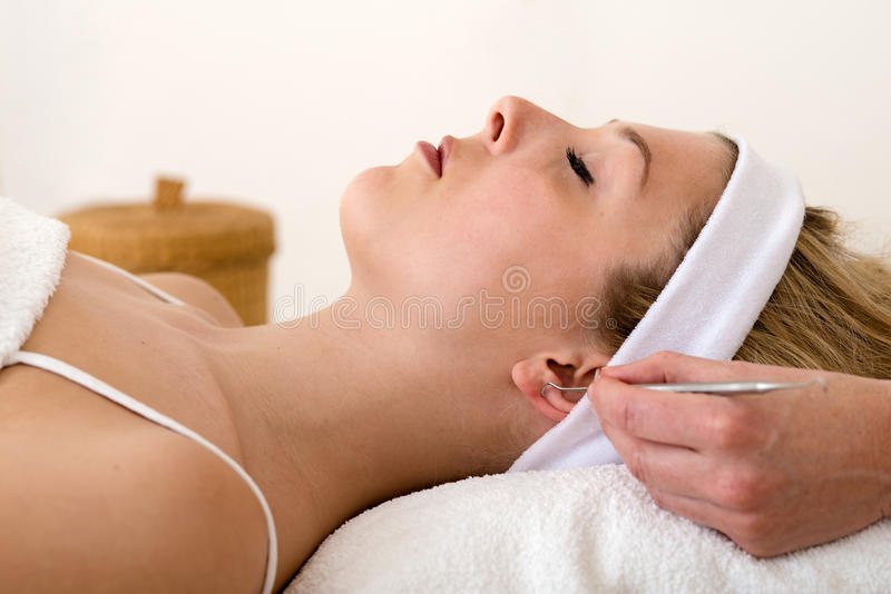 Homeopata que aplica técnicas auriculotherapy. foto de stock royalty free
