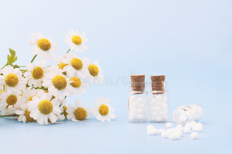 Homeopathic globules and glass bottles on blue background next to medicinal chamomile flowers. royalty free stock photo