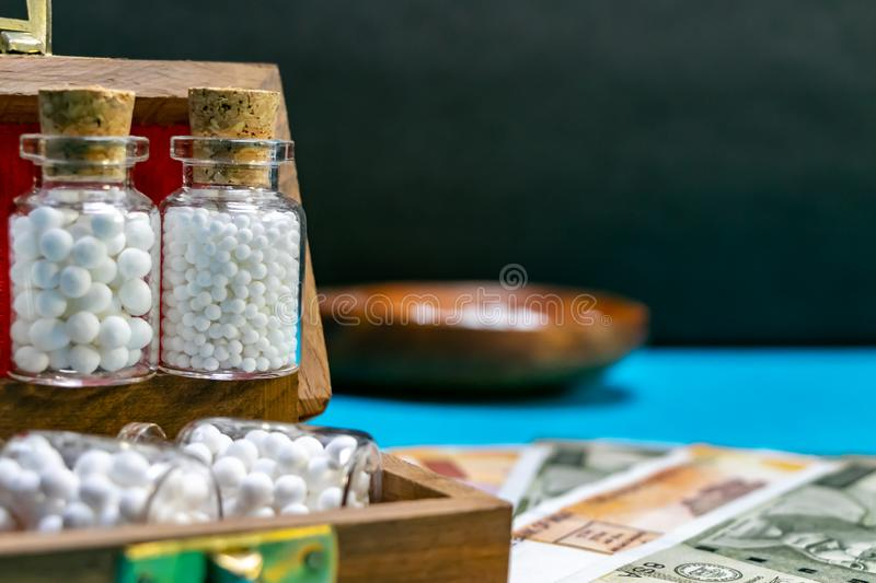Homeopathic medicine glass bottles of pills in wooden box on Indian currency and blue surface with blurred wood spoon and dark stock images