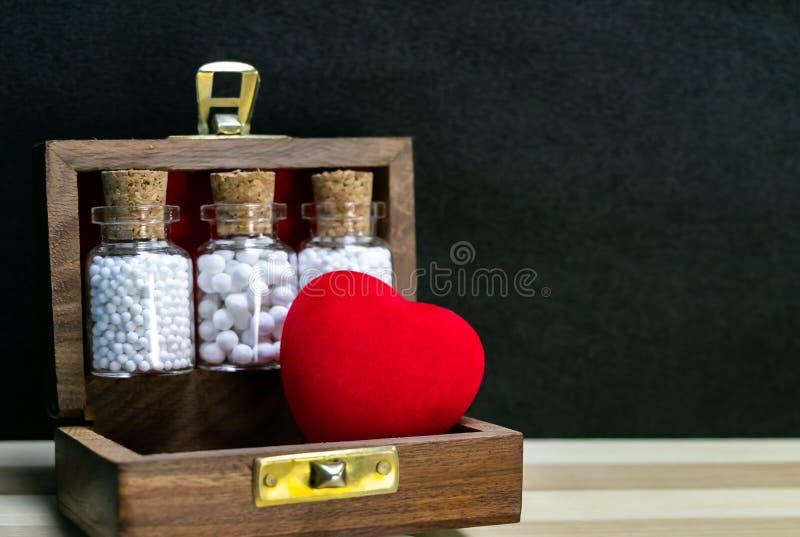 Homeopatia – Zamknięty widok homeopatii medycyny butelki z korkiem i sercem w drewnianym starym pudełku na tle drewnianym i ciemn zdjęcie royalty free