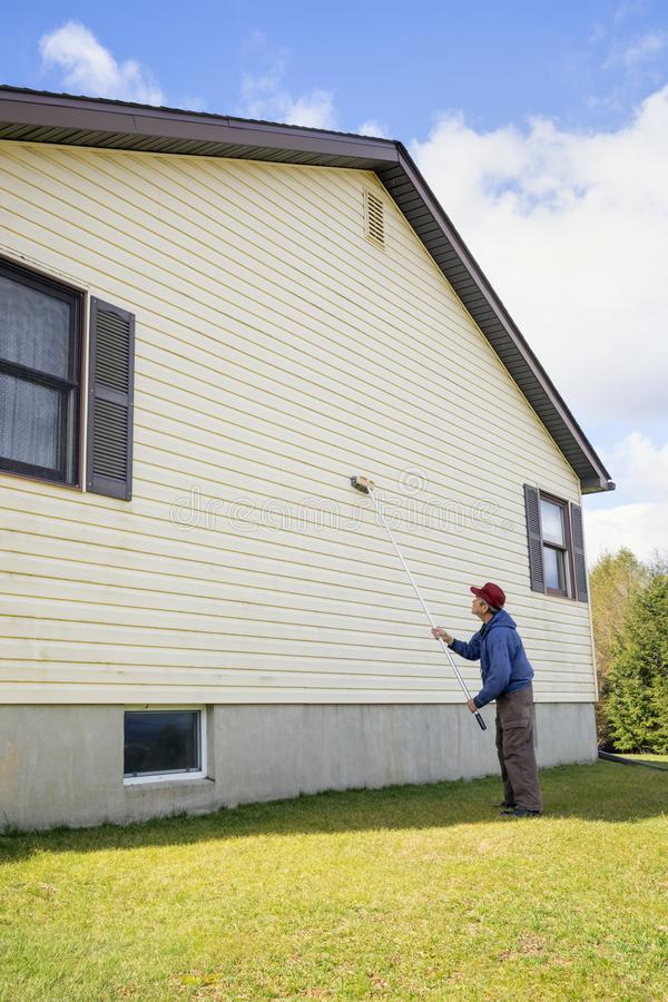 Homeowner washing house vinyl siding. Homeowner washing mold from vinyl siding on north side of house with brush and cleaning fluid stock photography