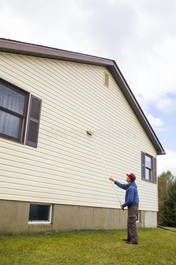 Homeowner washing house vinyl siding. Homeowner washing mold from vinyl siding on north side of house with brush and cleaning fluid royalty free stock image