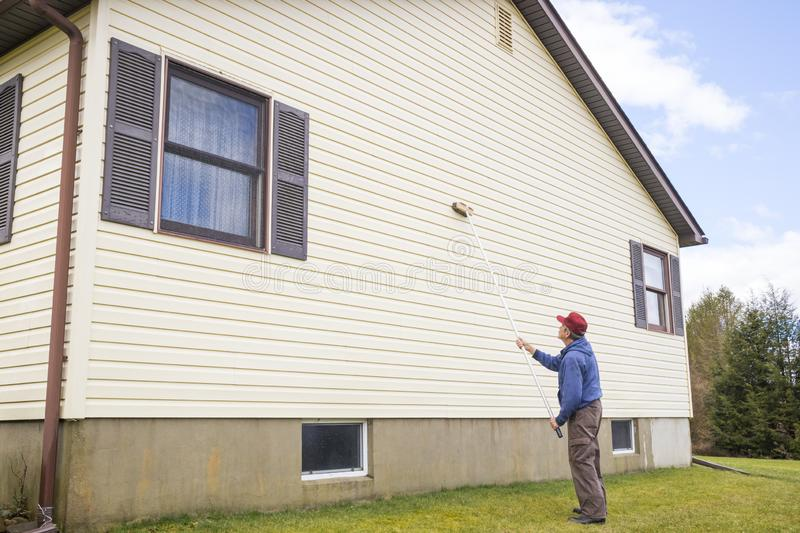 Homeowner washing house vinyl siding. Homeowner washing mold from vinyl siding on north side of house with brush and cleaning fluid stock photo