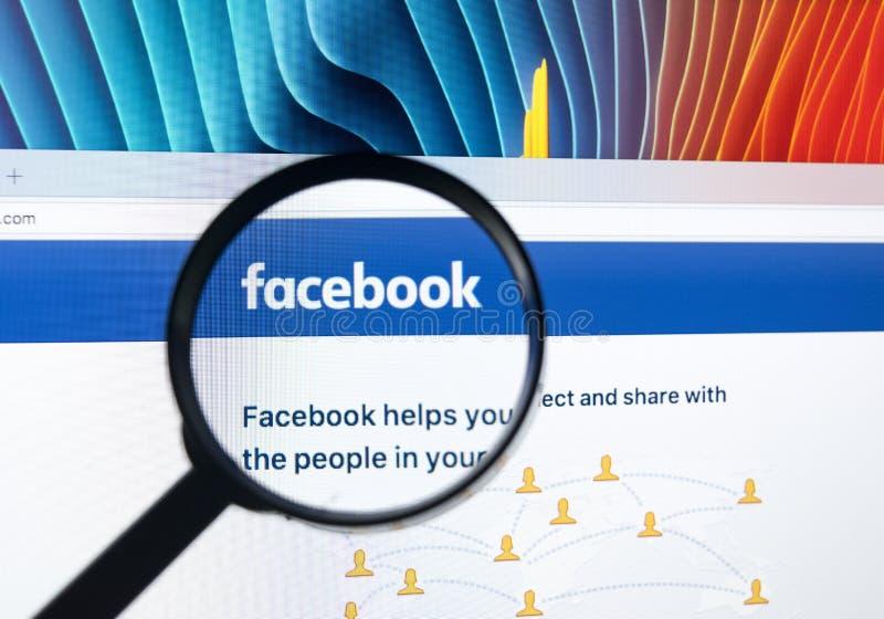Homepage av facebook com på den Apple iMac bildskärmskärmen under förstoringsglaset royaltyfria foton