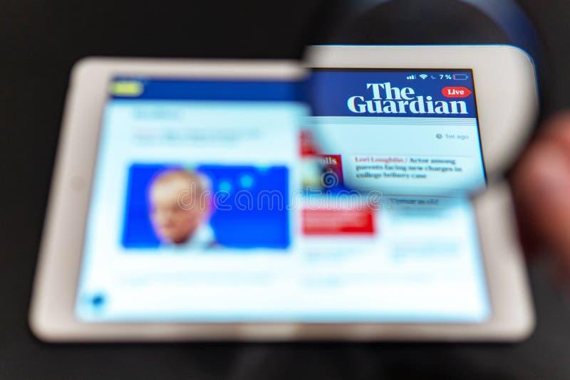 Homepage del sito Web di notizie di The Guardian sullo schermo della compressa Logo del canale di notizie del guardiano immagini stock libere da diritti