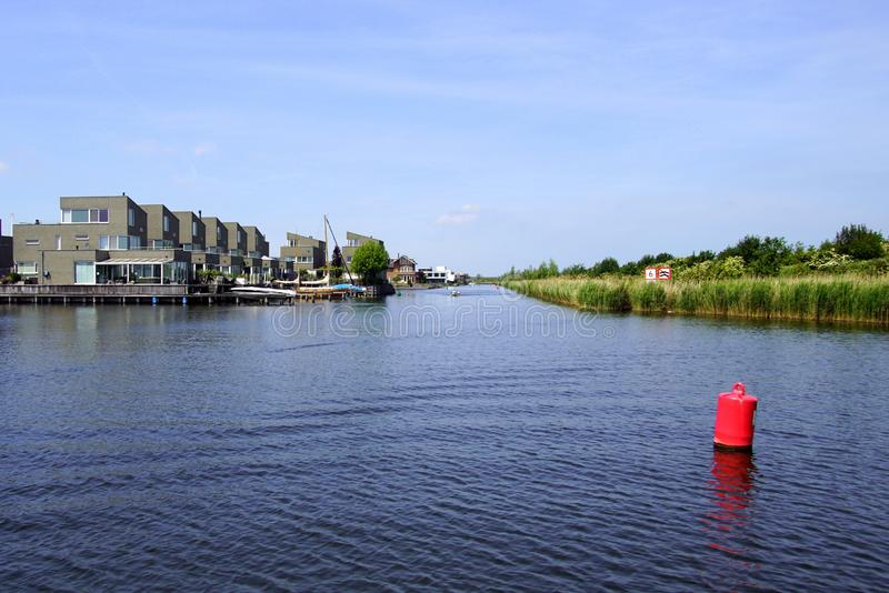 Homes along a Dutch waterway. Homes along a waterway in the Dutch city of Almere stock image