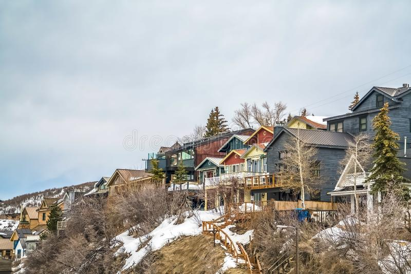 Homes with balconies on a mountain against sky filled with clouds in winter. Outdoor stairs, conifers, and leafless trees cna also be seen on the snow covered royalty free stock photo