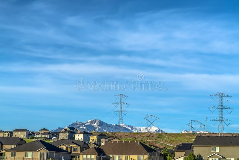 Homes on a hill with electricity towers and snow covered mountain background royalty free stock images