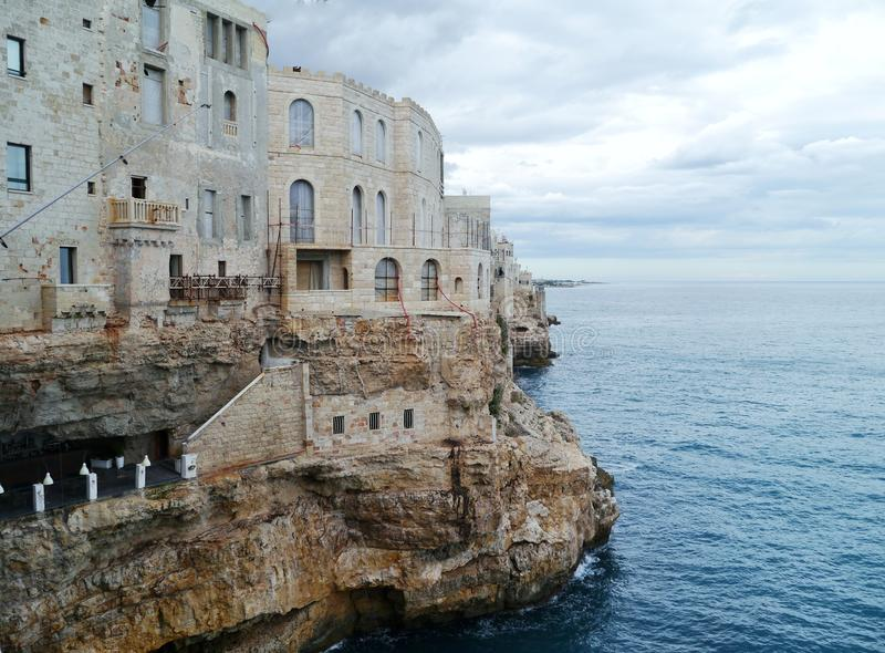 Homes in Polignano a mare in Italy. Houses on the rocks of the coast of Polignano a mare at the Mediterranean in Italy royalty free stock photo