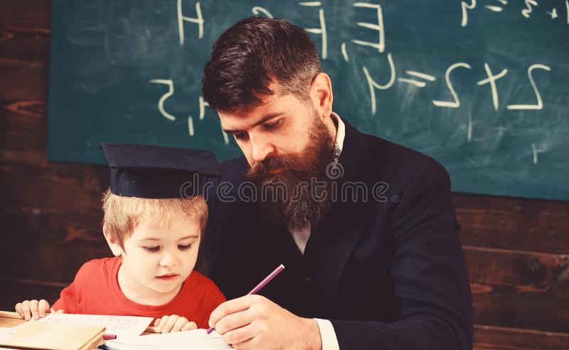 Homeschooling concept. Teacher in formal wear and pupil in mortarboard in classroom, chalkboard on background. Father royalty free stock photography