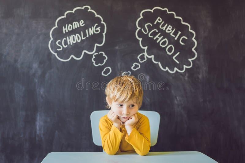 Homeschooling gegen allgemeine Schulen - der Junge sitzt am Tisch und wählt zwischen Hausunterricht und allgemeiner Schule - seie stockfotografie