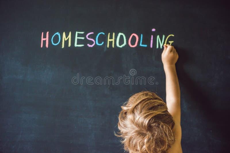homeschooling Kind, das auf Wort Homeschooling auf einem blackbo zeigt stockbild