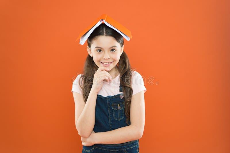 Homeschooling och privat kurs Bok p? hennes huvud Huvud för liten flickaboktak Orange bakgrund för liten flickabok royaltyfria foton