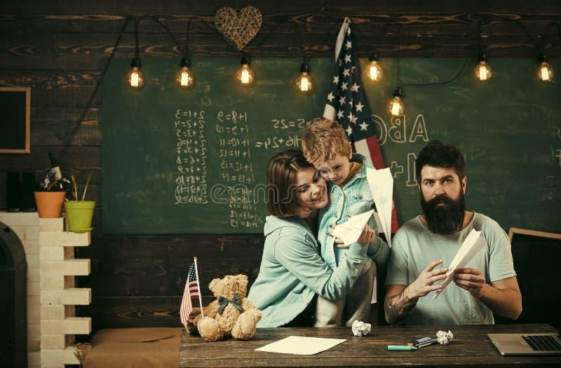Homeschoolingsconcept Ouders die zoon het Amerikaanse tradities spelen onderwijzen Amerikaanse familie bij bureau met zoon die do royalty-vrije stock foto