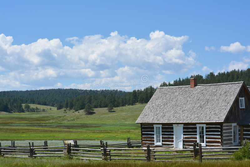 Homestead Log Cabin in Colorado Rocky Mountains. Original log home of settlers in Florissant, Colorado Rocky Mountains with split rail fence on a sunny day stock photo
