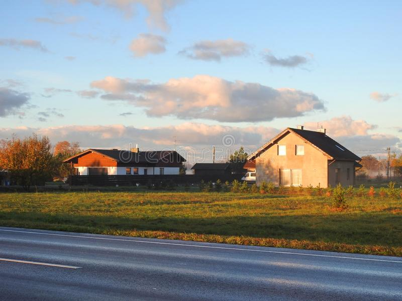 Homestead and wet way in morning time, Lithuania. Road, field and home in early morning in sunrise time stock images