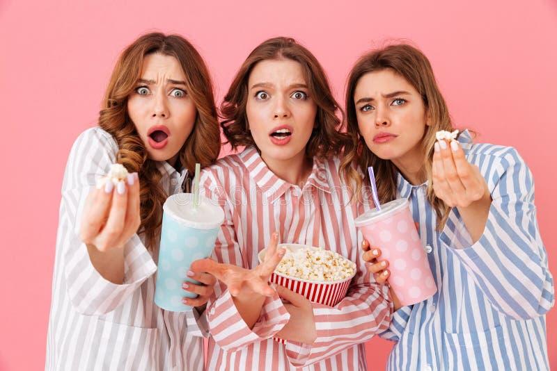 homewear的三个引人入胜的女孩吃玉米花和喝的 库存图片