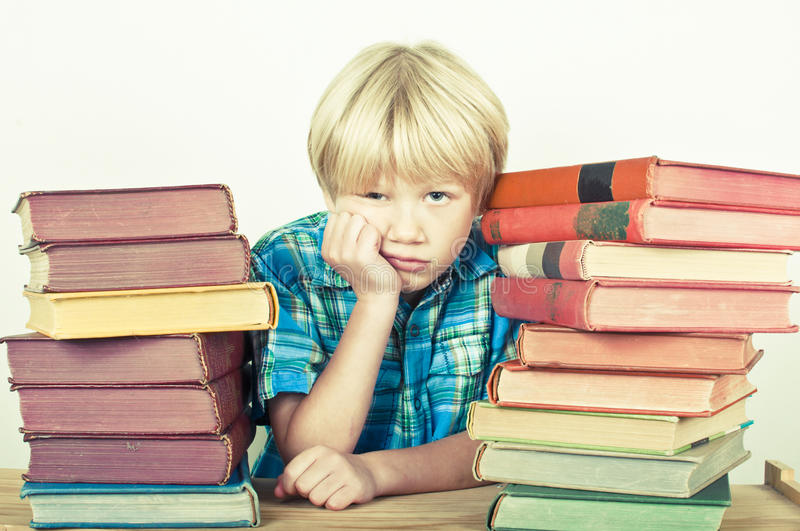 Homework. Bored child thinking about his pile of homework royalty free stock photography