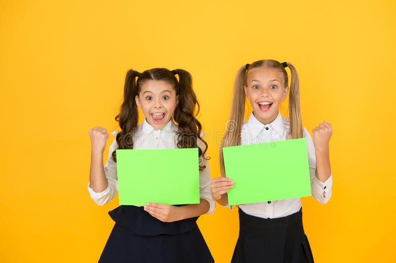 Homework done. Happy small children holding empty homework sheets on yellow background. Cute little girls smiling with. Blank green school posters for homework royalty free stock images