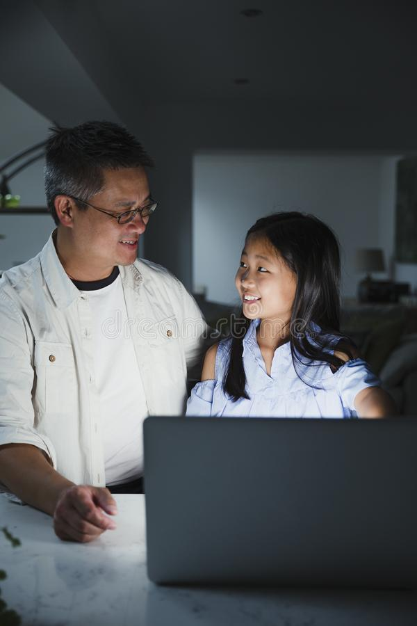 Homework Help from Dad. Little girl is getting help from her father while doing homework on the laptop at home stock photos